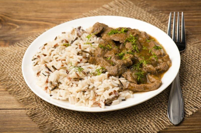 Gedämpftes Rindfleisch und Reis auf der weißen Platte auf hölzernem Hintergrund stockfoto