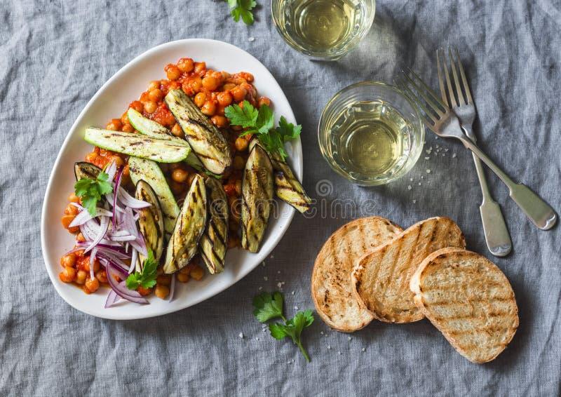 Gedünstete Kichererbsen in der Tomatensauce, in gegrillter Aubergine und in der Zucchini, Weißwein, grillten Brot - ein köstliche lizenzfreie stockbilder