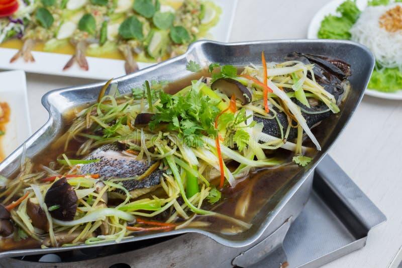 Ged?mpfter Barsch mit Sojaso?e in den Fischen formen Topf auf dem Tisch mit anderem Lebensmittel stockfotos