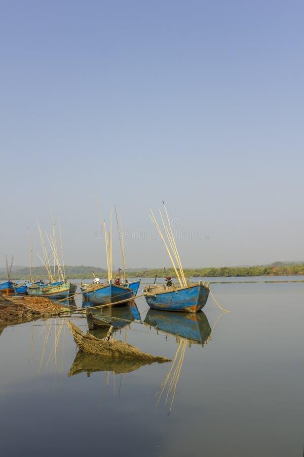 Gedaalde boot op riverbank op de achtergrond van grote blauwe verankerde boten stock fotografie