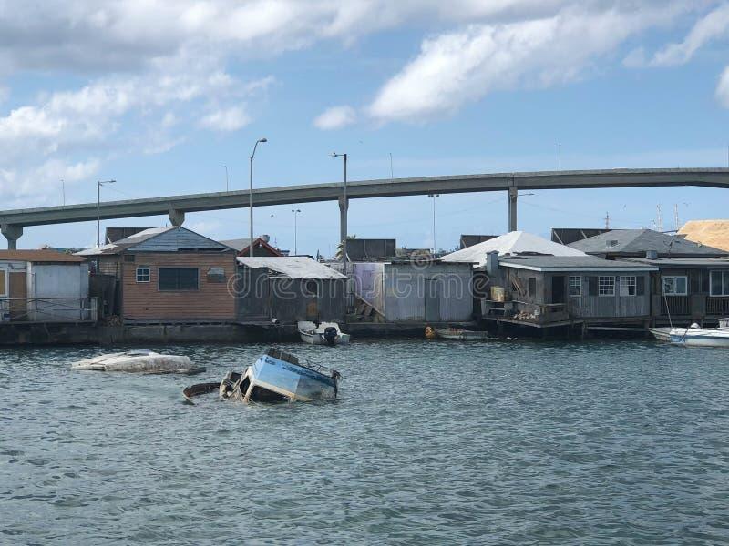 Gedaalde boten in water achter armen gereduceerde huizen royalty-vrije stock foto's