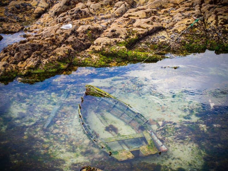 Gedaalde houten boot in het overzees stock foto's