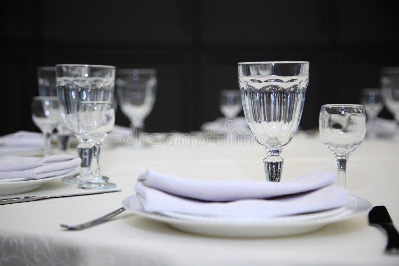 Gedeck in einem Restaurant Leere Gl?ser stellten in Gastst?tte ein Gedeck mit Gläsern, Tischbesteck und Platten lizenzfreie stockfotografie