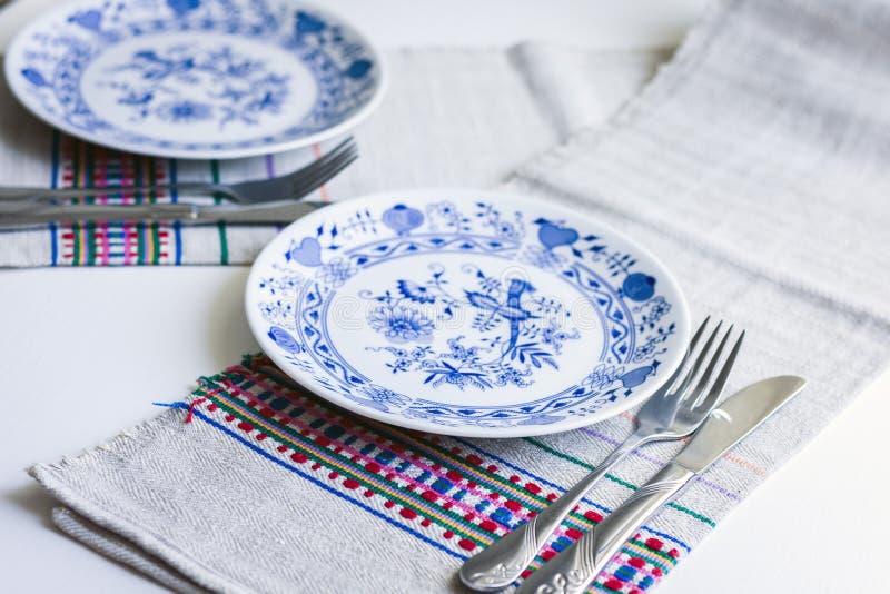 Gedeck für Abendessen: weiße und blaue Platten, eine Gabel, ein Messer auf einer gesponnenen Stoffserviette mit einem gestickten  lizenzfreie stockfotos
