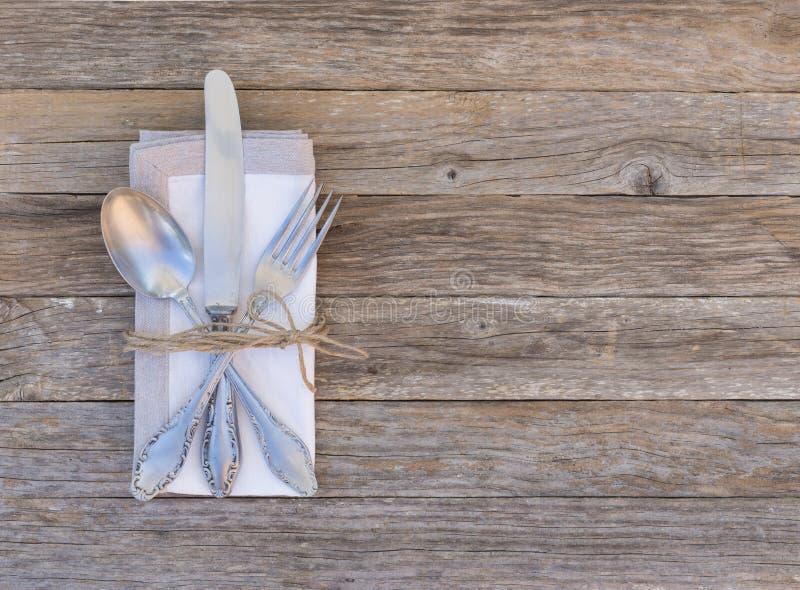 Gedeck mit elegantem Tischbesteck und Serviette auf Holztischhintergrund lizenzfreie stockfotografie