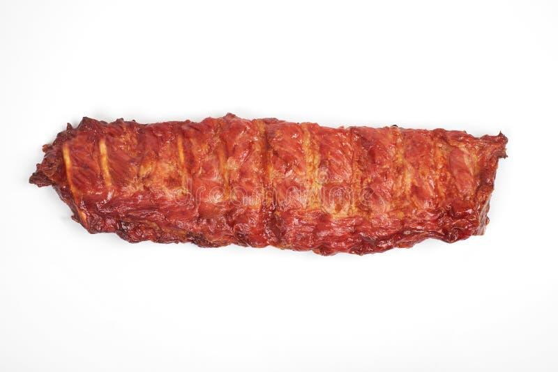 Gedeelte heerlijke kruidige gemarineerde die varkensvleesribben op witte achtergrond wordt geïsoleerd stock afbeeldingen