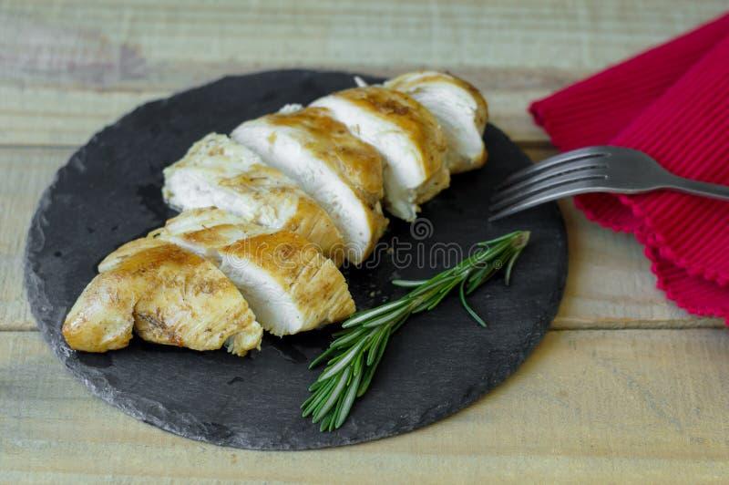 Gedeelte van geroosterde kippenborst met verse rozemarijnbladeren stock afbeeldingen
