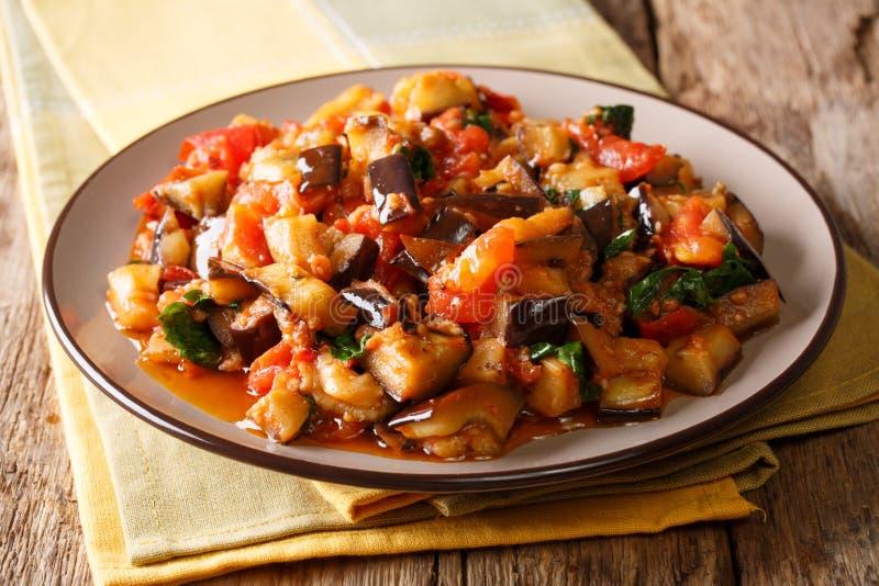Gedeelte van kruidig gebraden aubergine, tomaten en knoflook met parsle royalty-vrije stock foto