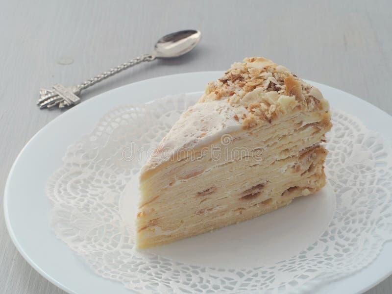 Gedeelte van multi gelaagde cake met grappige lepel Bladerdeegcake met crumbs wordt verfraaid die stock foto's