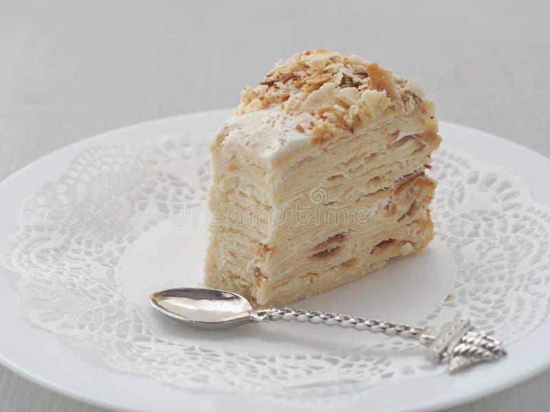 Gedeelte van multi gelaagde die cake, met grappige lepel wordt afgesneden Bladerdeegcake met crumbs wordt verfraaid die stock foto