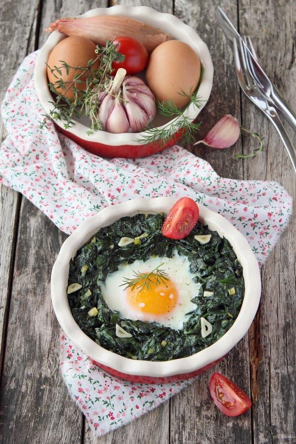 Gedeelte van vers gebakken ei met spinazie stock foto