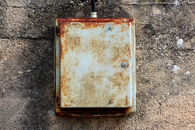 Gedeeltelijk geroeste dilapidated gesloten metaal elektrodoos opgezet op gebarsten oude concrete die muur aan dik zwart wordt ver royalty-vrije stock afbeelding