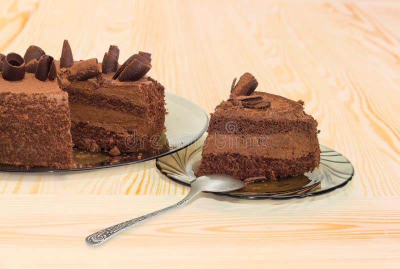 Gedeeltelijk gesneden chocolade gelaagde cake op de glasschotels royalty-vrije stock afbeeldingen
