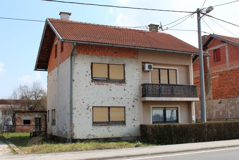 Gedeeltelijk vernieuwd huis in de voorsteden die door granaatscherven tijdens oorlog wordt beschadigd stock afbeelding