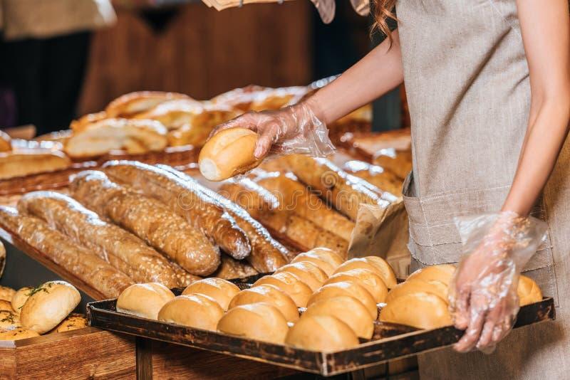 gedeeltelijke mening die van winkelmedewerker broden van brood schikken royalty-vrije stock afbeeldingen