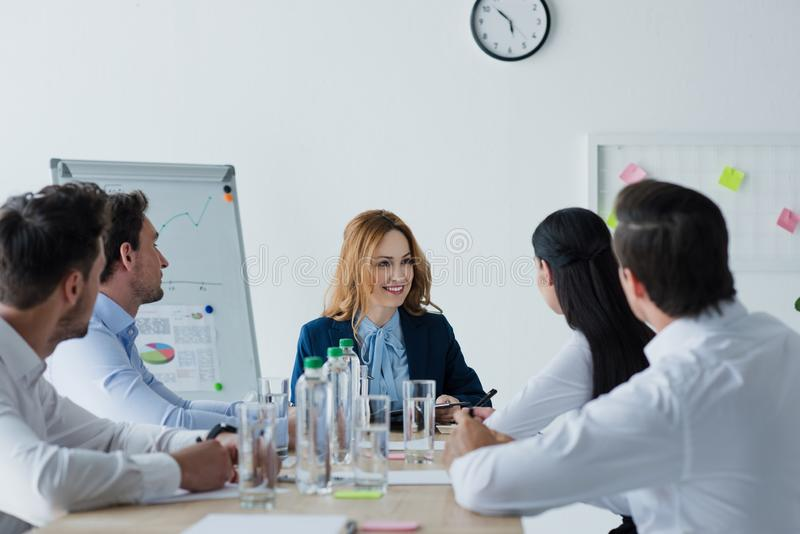 gedeeltelijke mening van bedrijfscollega's die bespreking hebben op het werk stock afbeelding