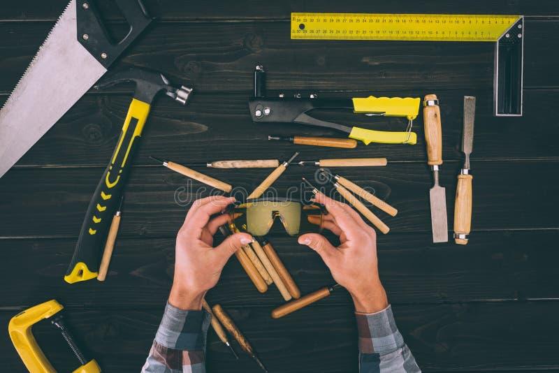 gedeeltelijke mening van de beschermende brillen van de timmermansholding in handen met diverse industriële rond hulpmiddelen royalty-vrije stock afbeeldingen