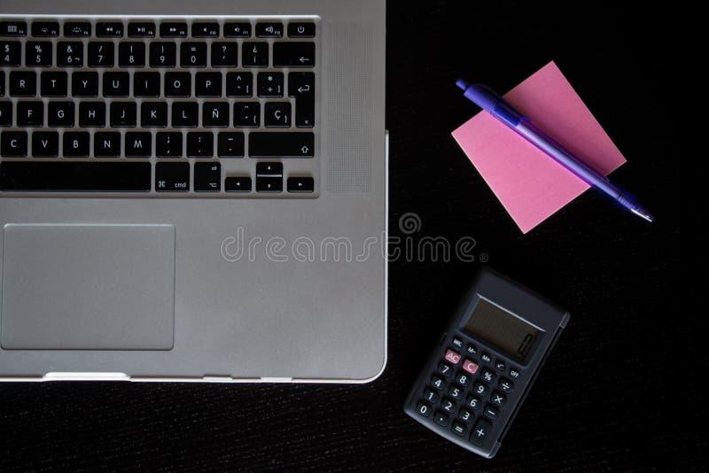 Gedeeltelijke mening van een zilveren toetsenbord van laptop met een calculator, en een roze post-itnota's met een potlood op een stock afbeelding