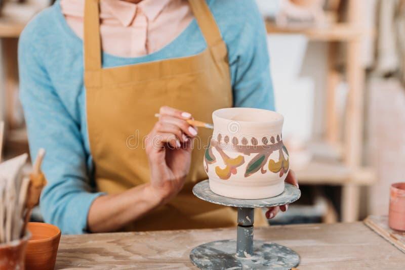 Gedeeltelijke mening van pottenbakker in schort traditioneel schilderen royalty-vrije stock afbeelding