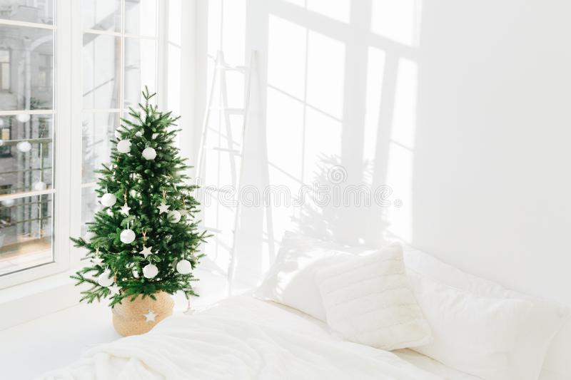 Gedeorbeerde feestelijke kerstboom in een witte klassieke slaapkamer met zachte bedden Binnenlandse winterwoning Cozy-seizoen Nie stock foto's