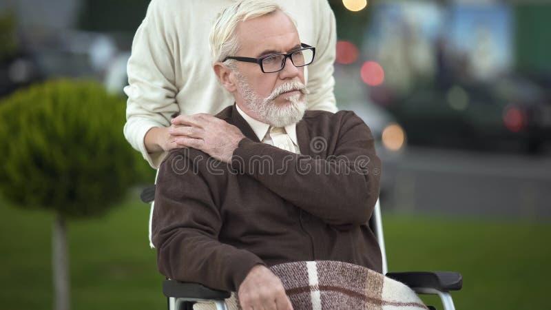 Gedeprimeerd gehandicapt bejaard mannetje die in rolstoel jonge vrouwelijke hand, familie strijken royalty-vrije stock foto