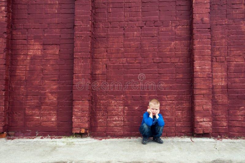 Gedeprimeerd kind dichtbij bakstenen muur royalty-vrije stock foto