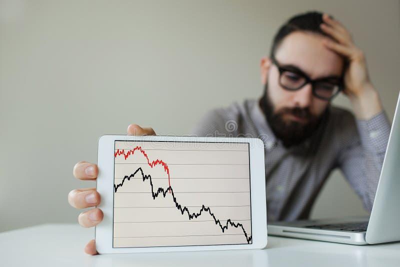 Gedeprimeerd zakenman leunend hoofd onder slechte effectenbeursgrafiek stock afbeelding
