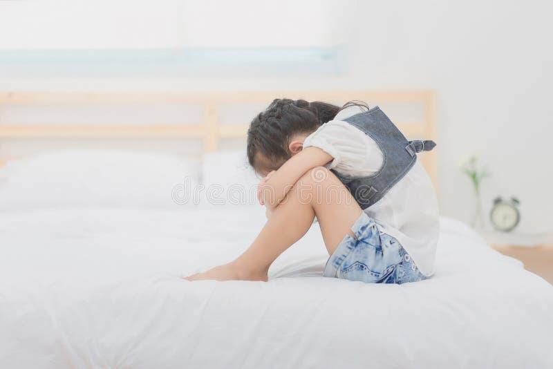 Gedeprimeerde Aziatische meisjes die op het bed zitten royalty-vrije stock foto