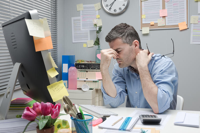 Gedeprimeerde beambte bij zijn bureau stock afbeelding