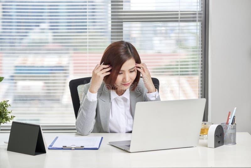Gedeprimeerde beklemtoonde jonge Aziatische bedrijfsvrouw met laptop die aan probleem lijden stock afbeeldingen
