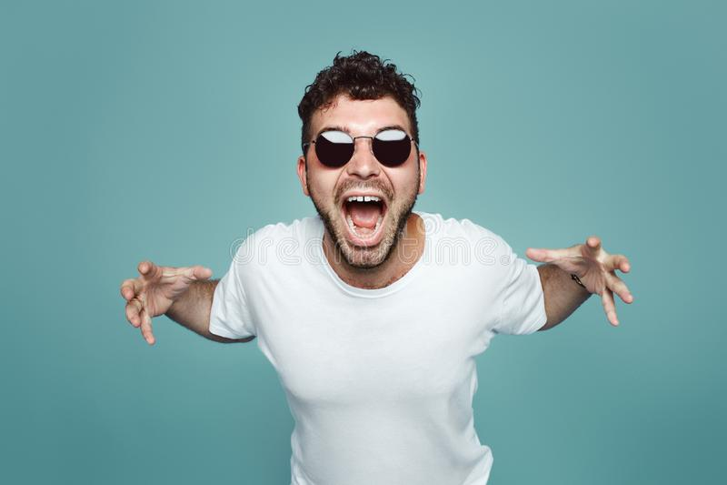 Gedeprimeerde boze hipster gebaarde mens met en zonnebril die, geïsoleerd over blauwe studiouachtergrond schreeuwen gillen royalty-vrije stock afbeelding