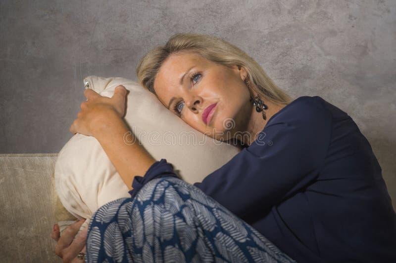 Gedeprimeerde en bezorgde mooie depressie en bezorgdheids gefrustreerd crisis aan gevoel lijden en blondevrouw die eenzaam bij ho royalty-vrije stock afbeeldingen