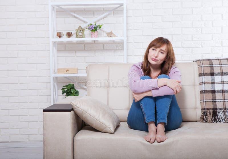 Gedeprimeerde en droevige midden oude vrouwenzitting met vastgeklemde knieën op bed, bus, bank thuis Exemplaarruimte en spot omho stock afbeeldingen