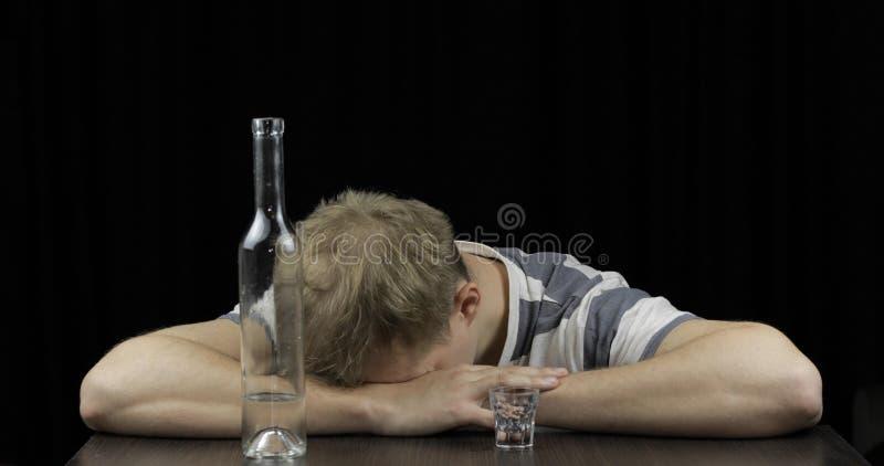 Gedeprimeerde gedronken mensenslaap alleen in een donkere ruimte Concept alcoholisme stock afbeelding