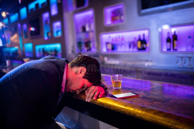 Gedeprimeerde gedronken mensenslaap met zijn hoofd op de lijst stock afbeelding