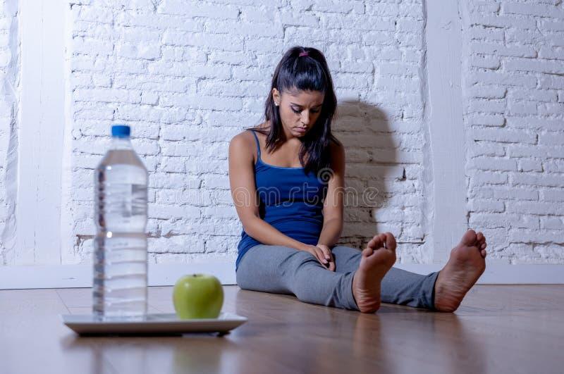 Gedeprimeerde het verhongeren jonge vrouw op appel en waterdieet stock foto