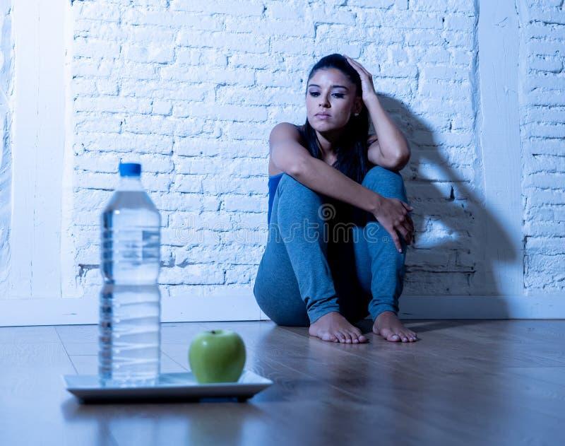Gedeprimeerde het verhongeren jonge vrouw op appel en waterdieet stock foto's