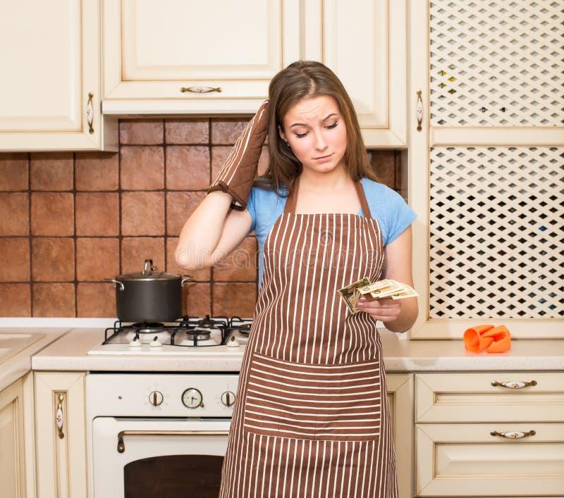 Gedeprimeerde jonge huisvrouw in schort en ovenwanten met binnen geld stock afbeeldingen