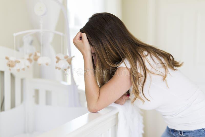 Gedeprimeerde jonge vrouw in babyruimte royalty-vrije stock foto