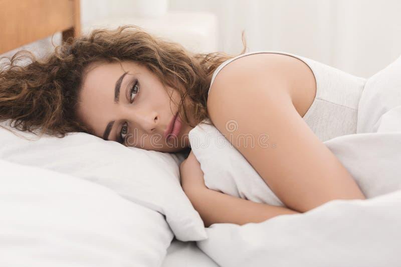 Gedeprimeerde jonge vrouw in bed liggen en verstoord feeeling die stock fotografie