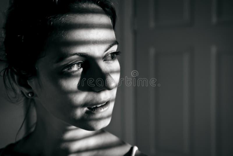 Gedeprimeerde jonge vrouw dichtbij venster thuis, close-up royalty-vrije stock fotografie