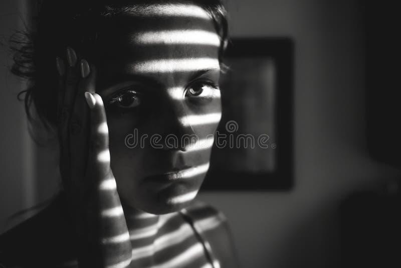 Gedeprimeerde jonge vrouw dichtbij venster thuis, close-up stock afbeeldingen