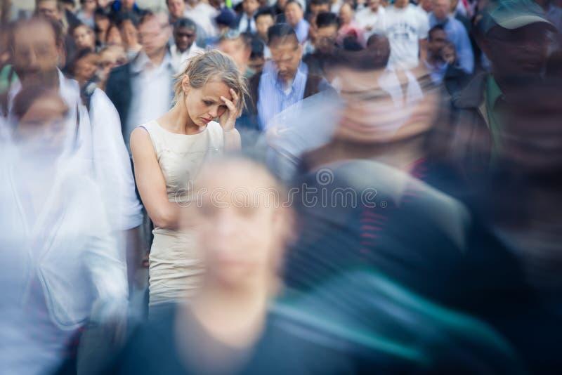 Gedeprimeerde jonge vrouw die alleen amid een menigte van mensen voelen royalty-vrije stock foto