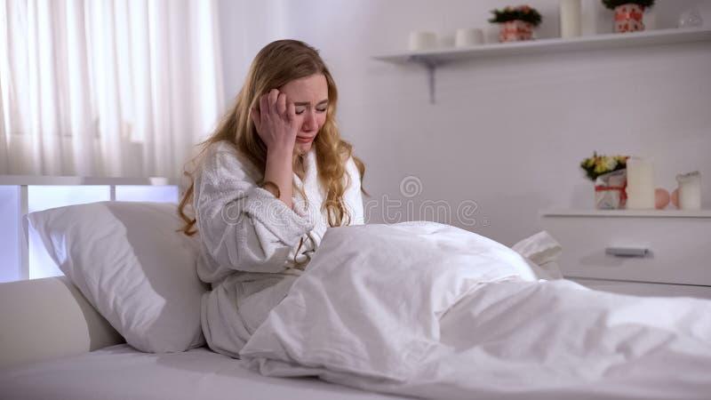 Gedeprimeerde jonge vrouw die in bed, pijn van relatief verlies, zorg en verdriet schreeuwen stock afbeeldingen