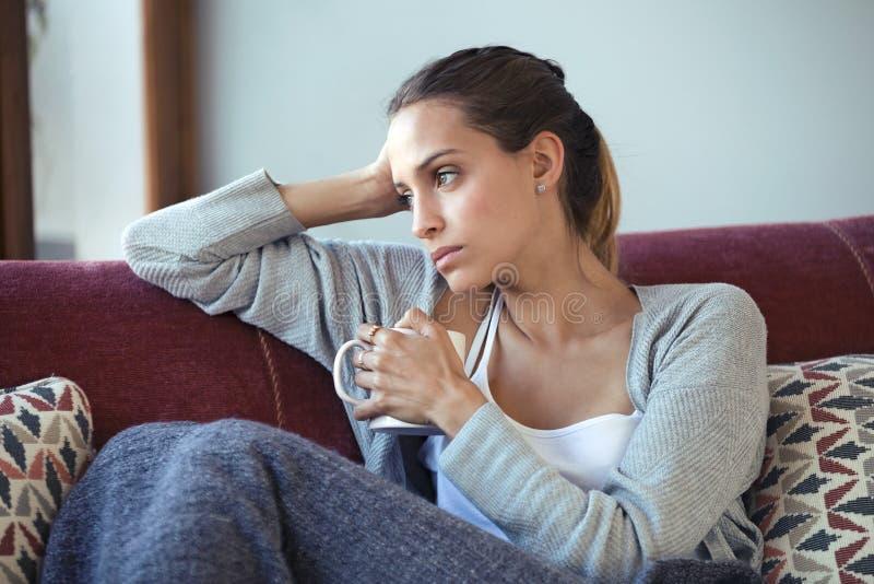 Gedeprimeerde jonge vrouw die over haar problemen denken terwijl thuis het drinken van koffie op bank stock afbeeldingen