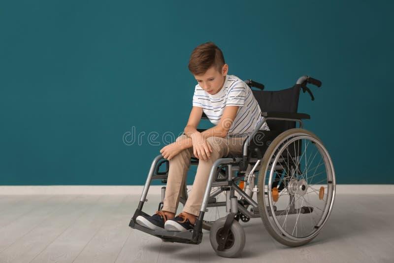 Gedeprimeerde jongen in rolstoel tegen kleurenmuur royalty-vrije stock fotografie