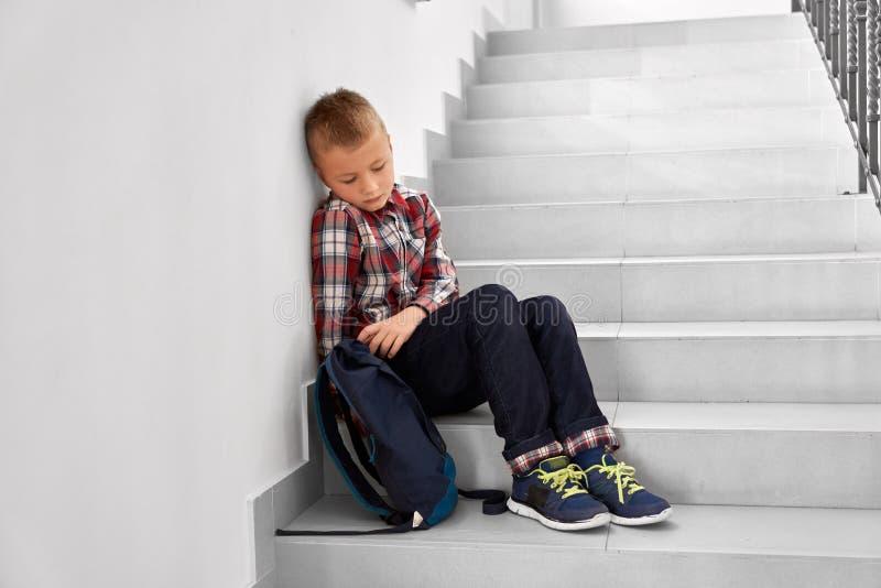 Gedeprimeerde jongenszitting op trap van lage school royalty-vrije stock foto's