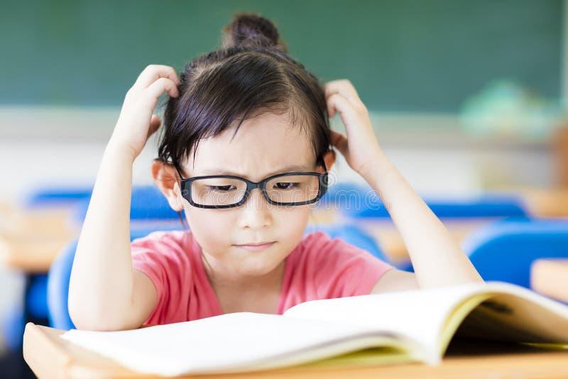 Gedeprimeerde meisjestudie in het klaslokaal stock afbeelding