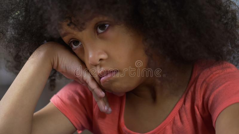 Gedeprimeerde meisjezitting die alleen en over haar gedrag, straf denken stock fotografie