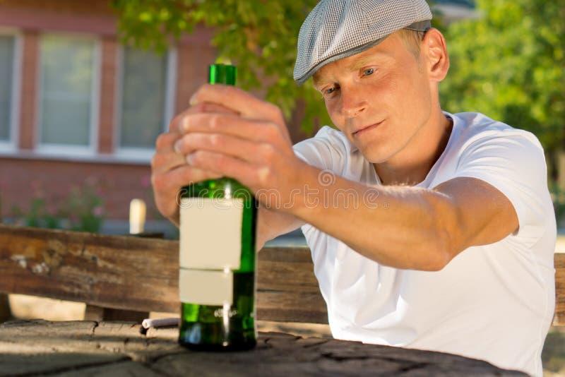 Gedeprimeerde mens die een fles van drank houden royalty-vrije stock foto's